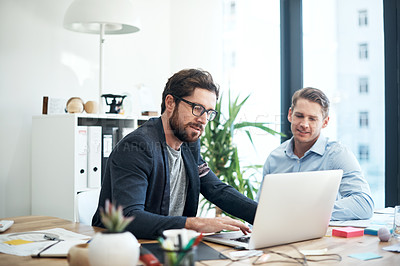 Buy stock photo Shot of two businessmen using a laptop together in an office