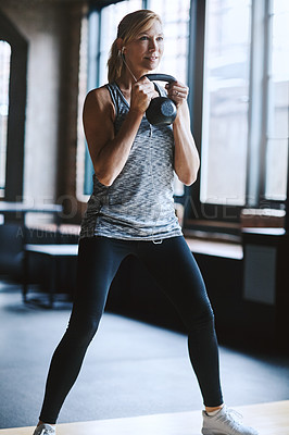 Buy stock photo Cropped shot of an attractive young woman listening to music while working out with a kettle bell in the gym