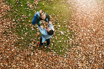 Buy stock photo Shot of a father and his little son playing in the autumn leaves outdoors