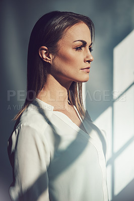 Buy stock photo Shot of a beautiful young businesswoman standing in a modern office