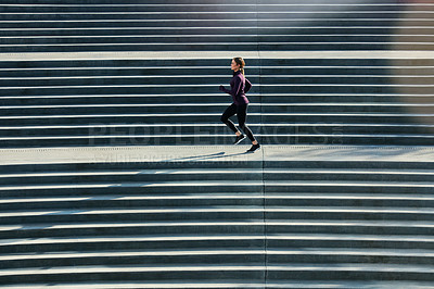 Buy stock photo Full length shot of an attractive young sportswoman running up and down stairs outside