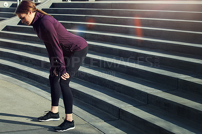 Buy stock photo Full length shot of an attractive young sportswoman resting after running up and down stairs outside