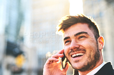 Buy stock photo Shot of a cheerful young man talking on his phone while waiting for a taxi to take him to work in the morning