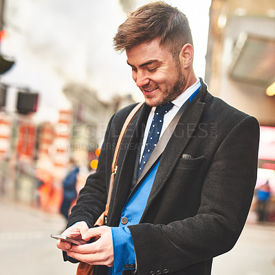 Buy stock photo Shot of a young well dressed man texting on his cellphone while waiting for a taxi to get him to work in the morning