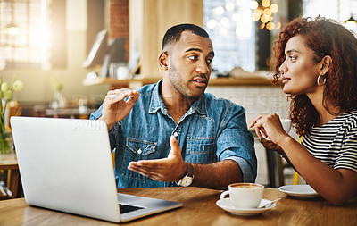Buy stock photo Cropped shot of a young couple working on a laptop while sitting in a coffee shop