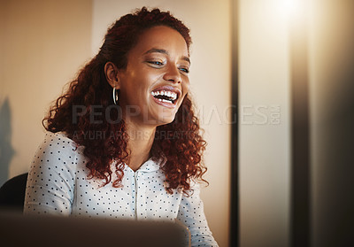 Buy stock photo Shot of a young businesswoman using a computer during a late night at work in a modern office
