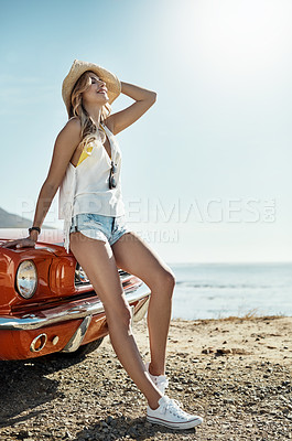 Buy stock photo Shot of an attractive young woman chilling against the hood of her car while on a road trip