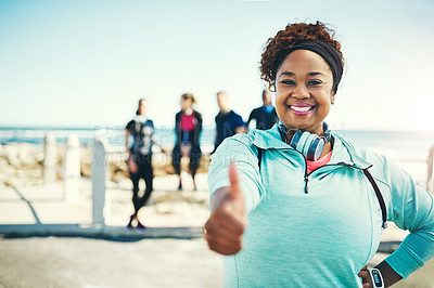 Buy stock photo Portrait of a sporty young woman showing thumbs up while exercising outdoors