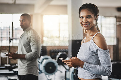 Buy stock photo Shot of a young woman using a mobile phone in a gym