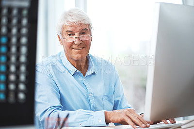 Buy stock photo Cropped portrait of a handsome senior businessman working on his computer at home