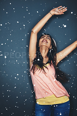 Buy stock photo Studio shot of an attractive young woman having fun with confetti against a dark background