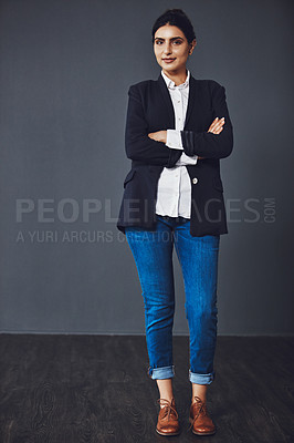 Buy stock photo Studio shot of an attractive and confident young businesswoman posing against a dark background