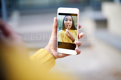 Buy stock photo Cropped shot of a beautiful young woman applying make up using her front camera on her cellphone as a mirror outside
