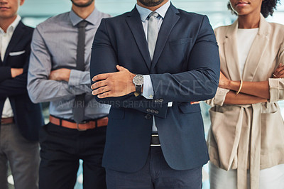 Buy stock photo Shot of a group of unrecognizable businesspeople standing with their arms folded inside of the office at work during the day