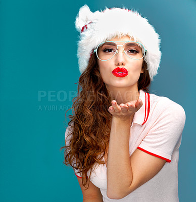Buy stock photo Studio portrait of a beautiful young woman blowing a kiss while wearing a Christmas hat against a blue background