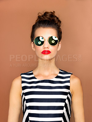 Buy stock photo Studio shot of a beautiful young woman wearing sunglasses while posing against a bronze background