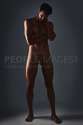 Buy stock photo Studio shot of a handsome and muscular young man posing in the nude against a grey background