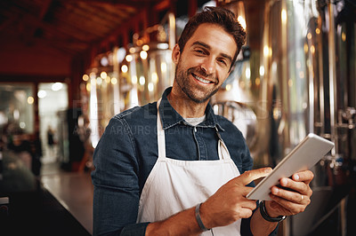Buy stock photo Portrait of a cheerful young barman browsing on a digital tablet while patiently waiting at the bar for customers inside of a beer brewery during the day