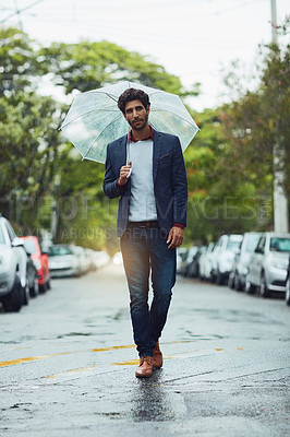 Buy stock photo Full length shot of a handsome young businessman on his morning commute in the rain