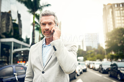 Buy stock photo Portrait of a mature businessman talking on a cellphone in the city