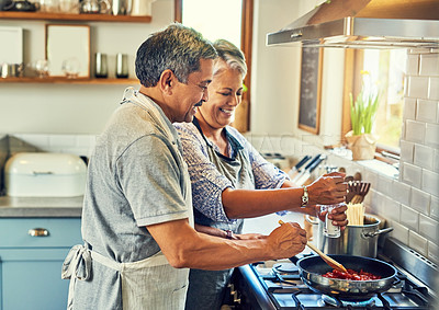 Buy stock photo Shot of a happy mature couple cooking a meal together at home