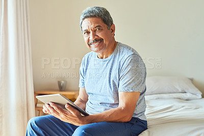 Buy stock photo Portrait of a cheerful mature man browsing on a digital tablet while being seated on his bed at home during the day