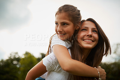 Buy stock photo Cropped shot of a young girl giving her younger sister a piggyback ride outdoors
