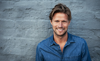 Buy stock photo Cropped portrait of a handsome young man standing against a grey brick wall