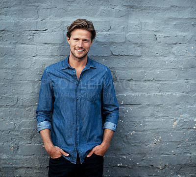 Buy stock photo Cropped portrait of a handsome young man standing with his hands in his pockets against a grey brick wall