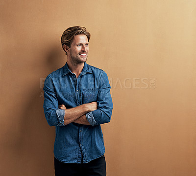 Buy stock photo Studio shot of a handsome young man standing with his arms folded against a bronze background