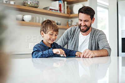 Buy stock photo Shot of a father and his little son using a digital tablet together at home