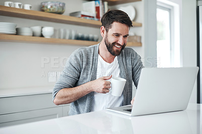 Buy stock photo Shot of a handsome young man using a laptop and having coffee at home