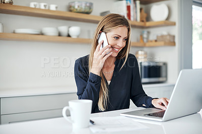 Buy stock photo Shot of an attractive young woman using a laptop and mobile phone at home