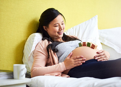 Buy stock photo Shot of a pregnant woman lying down with wooden baby blocks on her belly at home