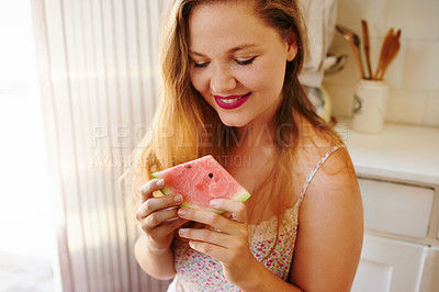Buy stock photo Shot of a cheerful young woman enjoying a slice of watermelon while being seated on a chair in the kitchen at home