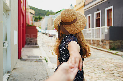 Buy stock photo POV shot of an unrecognizable woman holding her boyfriends hand while walking amongst colourful homes outside