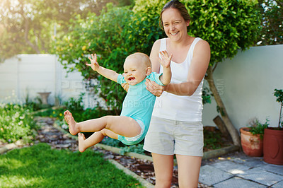 Buy stock photo Shot of a young woman and her adorable baby girl playing together in their backyard