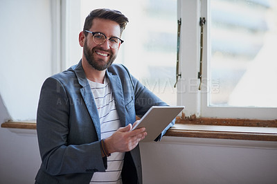 Buy stock photo Cropped portrait of a handsome young businessman working on a tablet while standing by his bedroom window