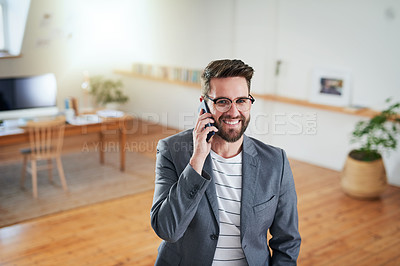Buy stock photo High angle shot of a handsome young businessman talking on his cellphone while standing in his home office