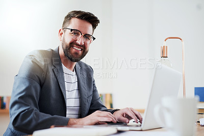 Buy stock photo Low angle portrait of a handsome young businessman working on his laptop while sitting in the home office