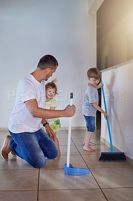 Buy stock photo Shot of two little siblings helping their father sweep the floor at home