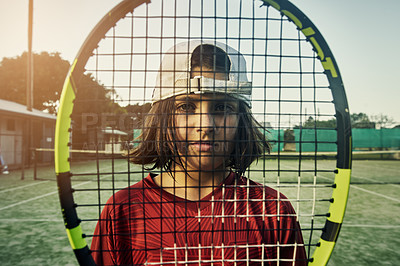 Buy stock photo Cropped portrait of a young boy looking through his racket while playing tennis