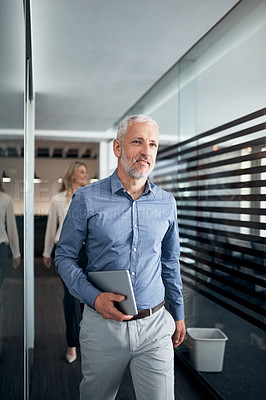 Buy stock photo Shot of a mature businessman walking down a corridor in an office