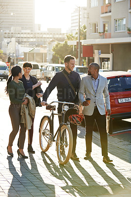 Buy stock photo Full length shot of four businesspeople chatting while on their way to work