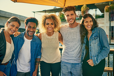 Buy stock photo Portrait of a group of young diverse friends spending the day outside on a rooftop