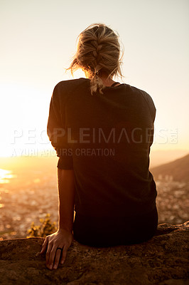 Buy stock photo Rearview shot of an unrecognizable young woman taking in the views during her hike in the mountains