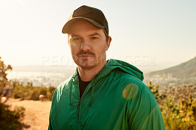 Buy stock photo Cropped portrait of a young man enjoying an early morning hike in the mountains