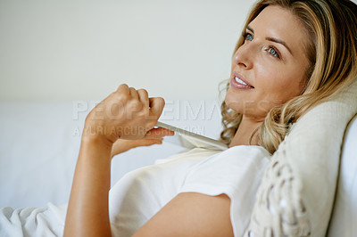 Buy stock photo Shot of a thoughtful young woman holding a digital tablet while relaxing on the sofa at home