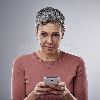 Buy stock photo Studio portrait of a mature woman using a mobile phone against a gray background