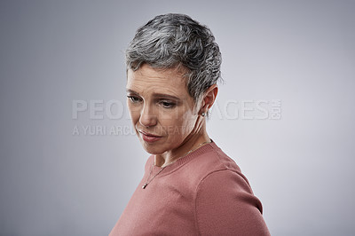 Buy stock photo Studio shot of a mature woman looking unhappy against a gray background